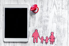 收养概念的大模型 在婴孩安慰者,家庭纸剪影附近的个人计算机在轻的背景顶视图copyspace的 库存照片