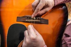 改变在声学吉他的一个人老被剥去的吉他串 免版税图库摄影