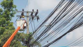 改变在缆车的新的电杆的亚裔工作者有 免版税图库摄影