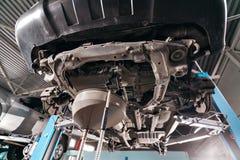 改变机器润滑油 工作在一辆被举的汽车下 免版税库存照片