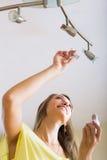 改变电灯泡的妇女 免版税库存照片