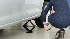 改变的轮胎的,使用汽车起重器的女孩螺旋千斤顶对推力汽车为为服务,顶起汽车 影视素材