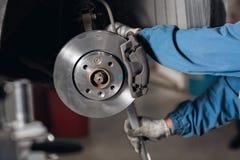 改变老驱动到在汽车的全新的闸圆盘在车库 汽车机械师修理 库存图片