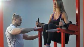 改正他的客户的个人教练员在健身房的锻炼期间 库存照片