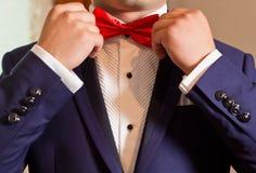 改正红色蝶形领结的一套白色衬衣和蓝色衣服的新郎 免版税库存图片