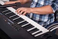 改进他的音乐技能的创造性的残疾绅士 图库摄影