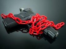 改革枪枝管制概念 在手枪附近的红色链子在黑色 库存照片