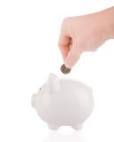 放一枚欧洲硬币入存钱罐 免版税库存照片