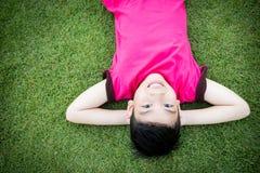 放下在草的小亚裔孩子 免版税库存图片