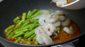 放与长的围场豆入黑聚四氟乙烯平底锅和混乱油煎的虾,香料,咖喱酱一起 股票录像