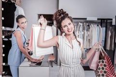 放光shopaholic与感到红色的嘴唇快乐在买新的礼服以后 免版税库存图片