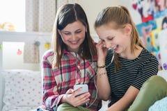 放出从手机的两个女孩音乐在卧室 免版税库存图片