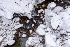 放出低谷岩石的山小河盖在雪,冬天风景,航拍 免版税库存照片