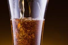 放出在金黄背景的一个啤酒杯 免版税库存图片