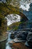 放出赛跑在一座传统老石桥梁下在Zagori希腊 免版税库存照片