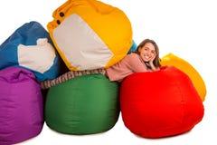 放在装豆子小布袋椅子之间的年轻微笑的妇女 免版税库存照片