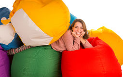 放在装豆子小布袋椅子之间的年轻笑的妇女 免版税库存照片