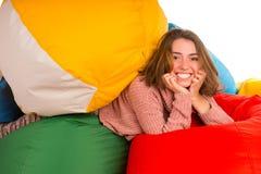 放在装豆子小布袋椅子之间的年轻逗人喜爱的笑的妇女 库存照片