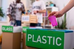 放塑料的女孩入排序在生态组织的箱子废弃物 图库摄影