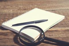 放大器和笔在笔记薄在木书桌上 免版税图库摄影