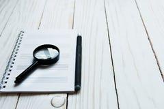 放大器,笔记本,在一个白色木背景的笔 免版税库存图片