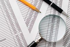 放大镜、笔和铅笔在报告顶部 免版税图库摄影