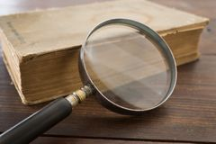 放大镜和一本旧书 免版税库存照片