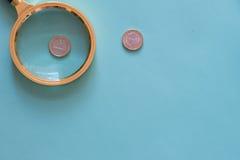 放大镜和金钱在中立绿色背景 Тop v 库存图片
