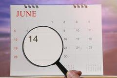放大镜在日历您能在手中看第十四天 图库摄影