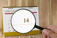 放大镜在日历您能在手中看第十四天 库存照片