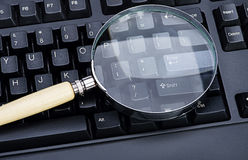 放大镜的图象在一个黑键盘的 库存图片
