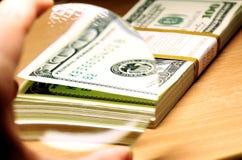 放大镜瞄准厚实的堆一百元钞票 图库摄影
