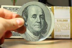 放大镜瞄准厚实的堆一百元钞票 免版税库存照片