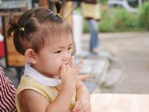 放她的手指的小亚裔女婴入她的嘴 库存照片