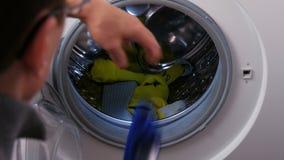 放孩子的橄榄球衬衣的一个人入洗衣机 影视素材