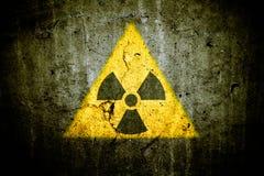 放射性原子核在三角形状的致电离辐射危险警告信号绘了巨型的破裂的混凝土墙 库存图片