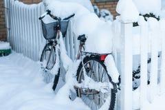 放弃与积雪的自行车倾斜了在a前面的篱芭 免版税库存图片