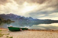 放弃钓鱼在银行的明轮船 早晨Alps湖 免版税库存图片