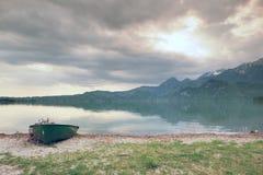 放弃钓鱼在Alps湖银行的明轮船  发光由阳光的Morning湖 图库摄影