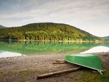 放弃钓鱼在Alps湖银行的明轮船  发光由阳光的Morning湖 免版税库存图片