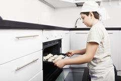 放新月形面包的男孩入烤箱 图库摄影