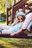 放松不快乐的儿童的女孩在夏天庭院里sunbed 免版税库存照片