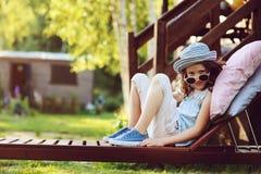 放松不快乐的儿童的女孩在夏天庭院里sunbed 库存图片