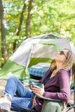 放松与一个杯子的妇女咖啡在早晨在fa的露营地 免版税库存图片