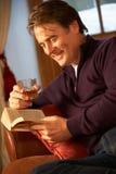 放松与书的人坐沙发 免版税图库摄影