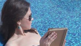 放松与书的美丽的妇女由水池,晒日光浴在海滩 影视素材