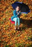 放松与伞的女孩在秋季公园 免版税库存图片