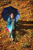放松与伞的女孩在秋季公园 库存图片