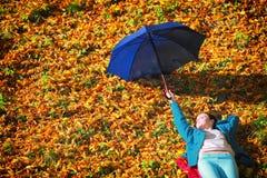 放松与伞的女孩在秋季公园 库存照片