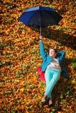 放松与伞的女孩在秋季公园 图库摄影